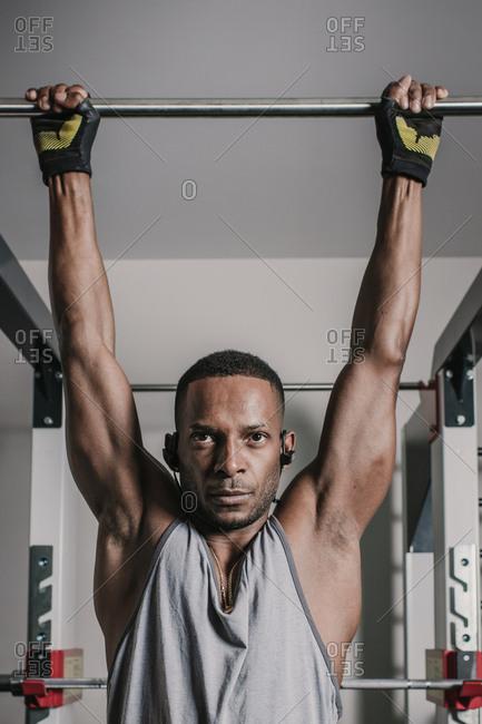Black guy hanging on bar in gym