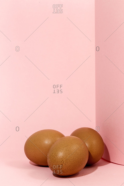 Raw eggs on pink background. High contrast