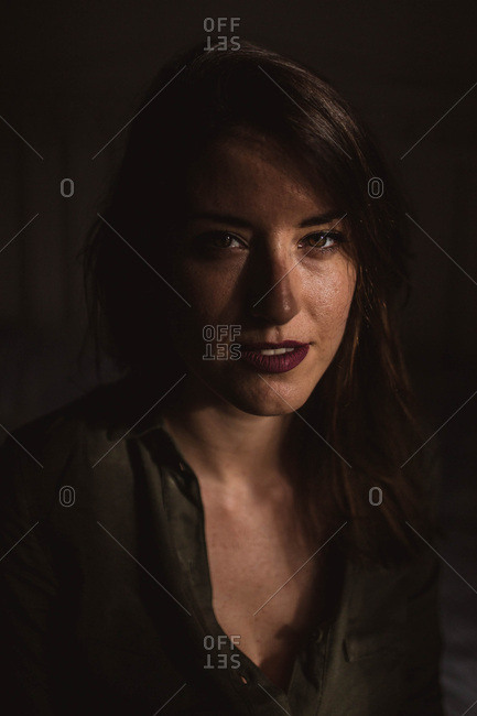 Attractive young female with good makeup smiling and looking at camera while sitting in dark room