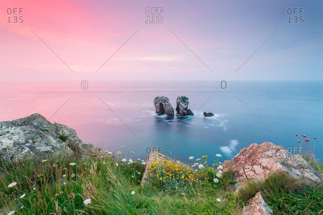 Picturesque view of two rocks in middle of calm sea against blue and pink morning sky