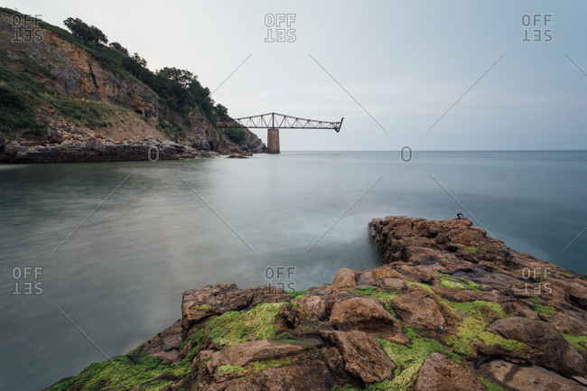 Amazing view of modern unfinished bridge located near cliff over calm water