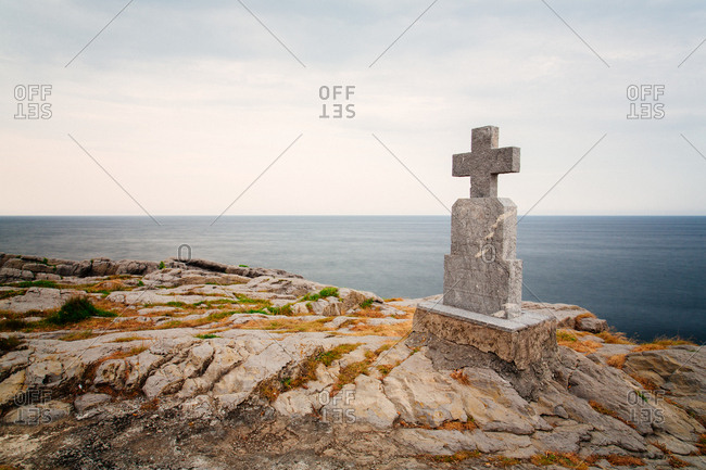 November 8, 2018: Ancient grave with stone cross located of rocky cliff near sea on cloudy day