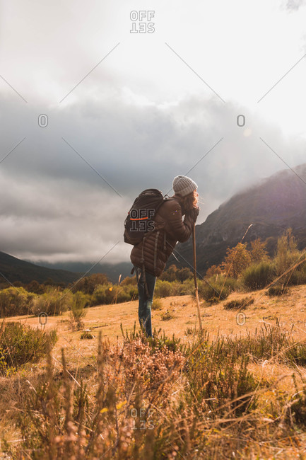 Side view of lady in hat and ski jacket with knapsack and walking stick walking on meadow near mountain in clouds in Isoba, Castile and Leon, Spain