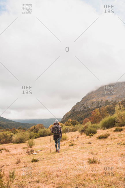 Back view of lady in hat and ski jacket with knapsack and walking stick walking on meadow near mountain in clouds in Isoba, Castile and Leon, Spain