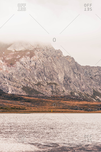 Person in yellow raincoat going on shore of lake near a mountain in Isoba, Castile and Leon, Spain