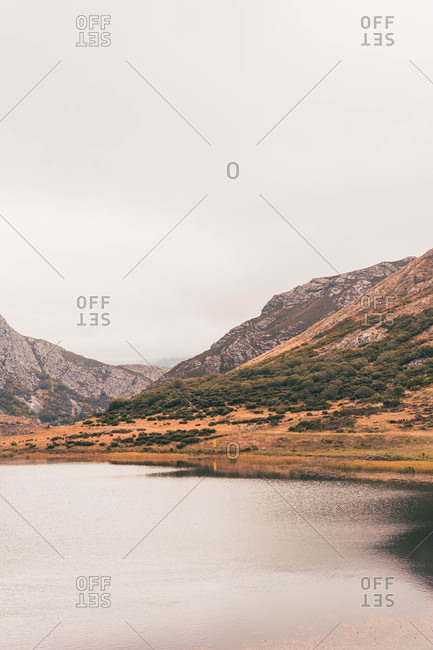Person in yellow raincoat going on shore of lake near wigwam and hill in Isoba, Castile and Leon, Spain