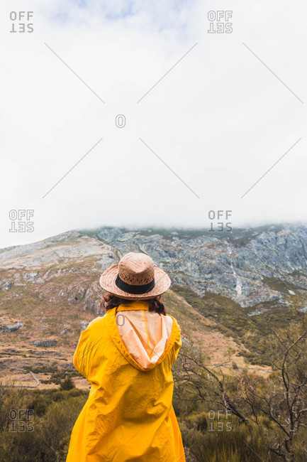 Back view of lady in hat and yellow raincoat looking at the landscape in Isoba, Castile and Leon, Spain