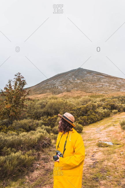 Side view of lady in hat and yellow raincoat with camera looking at the landscape in Isoba, Castile and Leon, Spain