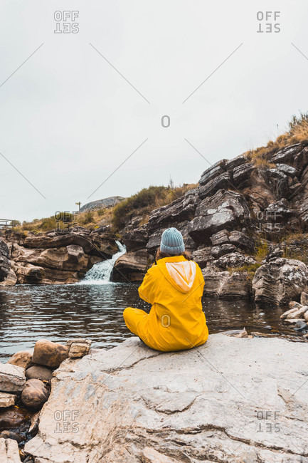 Back view of woman in hat and yellow raincoat sitting in stones and shooting rift of river between rock hills on camera in Isoba, Castile and Leon, Spain