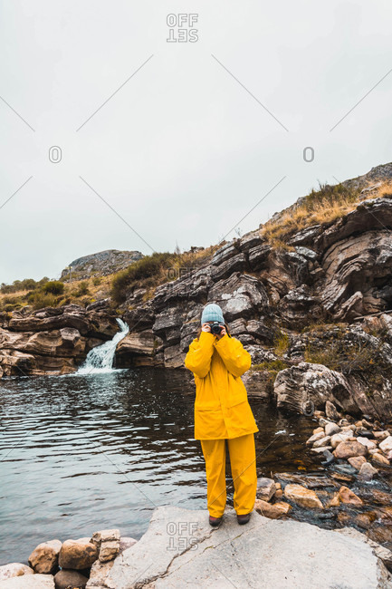 Woman in hat and yellow raincoat standing in stones and shooting rift of river between rock hills on camera in Isoba, Castile and Leon, Spain