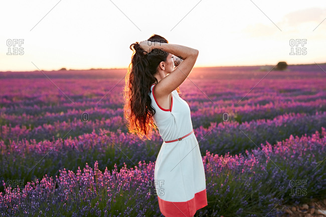 Woman standing between big violet lavender field at sunset