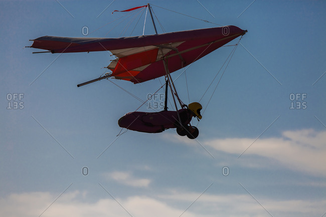Side view of unrecognizable person in helmet flying on�modern hand glider on background of cloudy blue sky