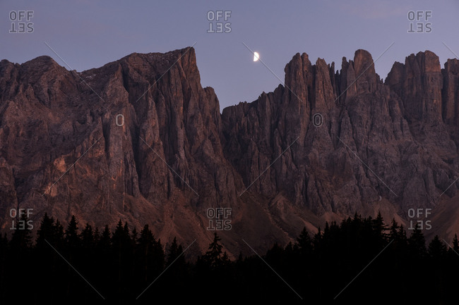 Red rocky mountain peaks at moon rise time over twilight sky. Dolomites Alps, Italy