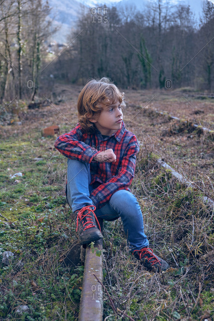 Boy sitting on old railways between meadow