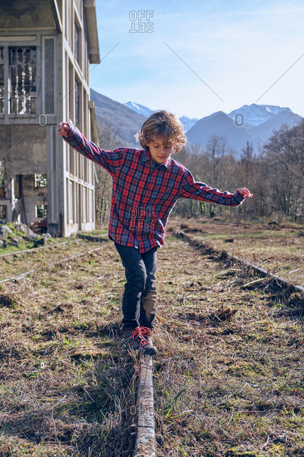 Little child in casual wear with hands to sides near rail tracks, broken building, high mountains and blue sky in countryside