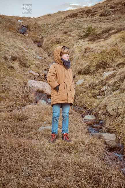 Adorable boy in warm clothes keeping hands in pockets and looking away while standing on slope of hill near small creek in autumn countryside