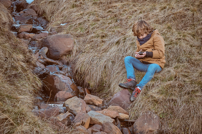 Sweet boy in warm clothes sitting on dry grass near creek with clean water in autumn countryside