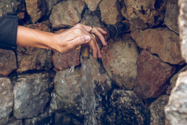 Hand of anonymous female lying on tap with clean fresh water near aged stone wall