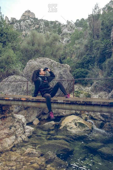 Beautiful woman looking at distance through modern binoculars while sitting on small bridge over calm stream in park Soller, Spain