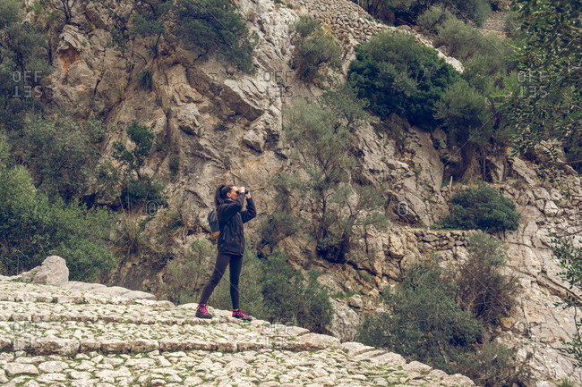 Beautiful woman looking at distance through modern binoculars while standing on stone path in majestic park