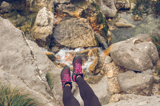 From above shot of anonymous woman in leggings and sneakers hanging over amazing rough rocks and tiny creek with fresh water