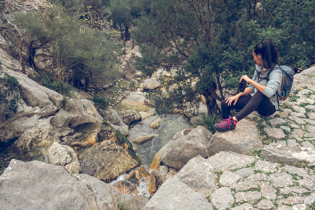 Woman looking away and holding binoculars while sitting on stone path over calm stream with clean water in wonderful park in Soller, Spain