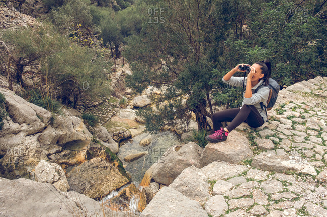 Beautiful woman smiling and looking at distance through modern binoculars while sitting on stone path over calm stream in park Soller, Spain