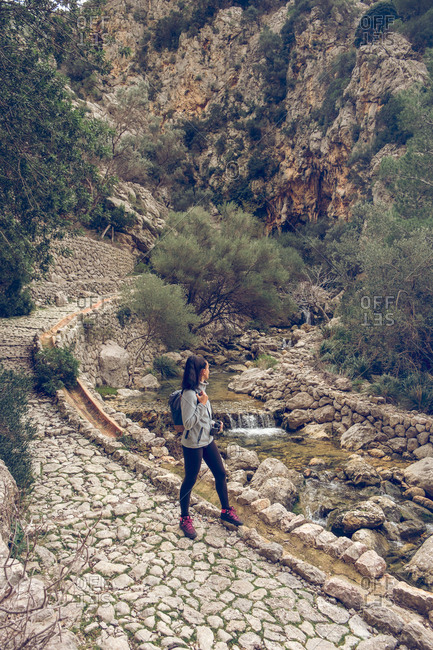 Female with backpack standing on a stone path near a river with fresh clean water in amazing park