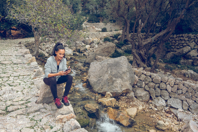 Attractive female in casual outfit browsing modern smartphone while sitting on stone near tiny creek with fresh clean water in wonderful park