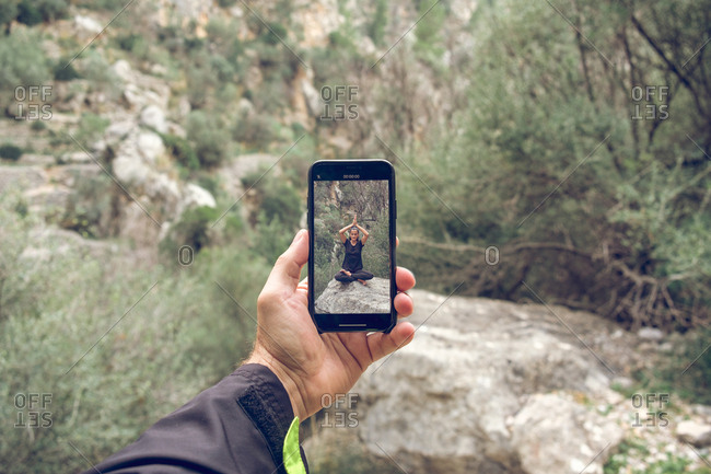 Hand of unrecognizable person holding modern smartphone with picture of female meditating on rock on background of magnificent park
