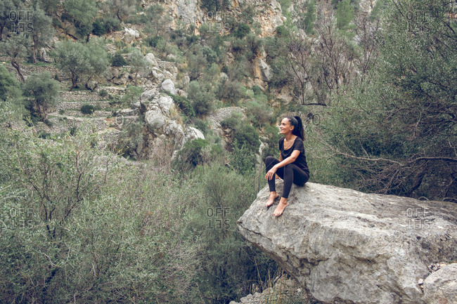 Attractive female in casual outfit sitting in edge of rough stone near wonderful mountain in beautiful park