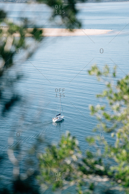 Magnificent view of modern yacht floating on rippling water of amazing sea from behind branches of green trees in Cantabria, Spain