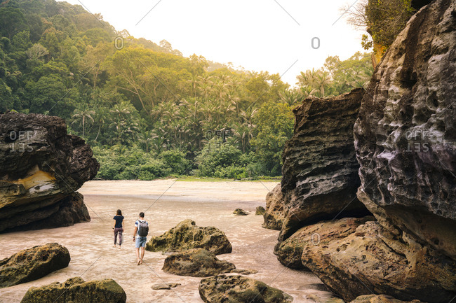 Back view young couple between rocks on sand beach near green tropical forest in Malaysia