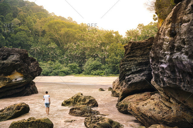 Back view young guy between rocks on sand beach near green tropical forest in Malaysia