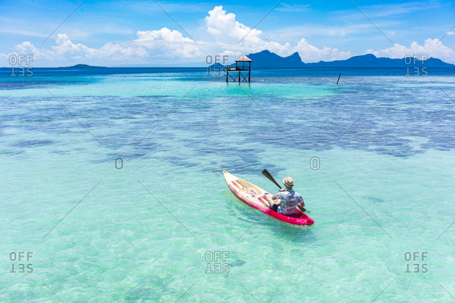 Back view male boating on canoe with paddle on amazing azure sea and blue sky in Malaysia