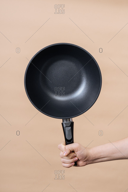 Hand holding frying pan against a nude background
