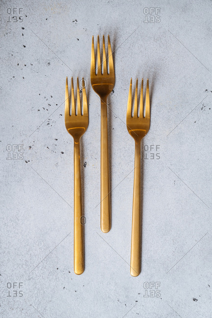 Trio of gold forks on a speckled counter