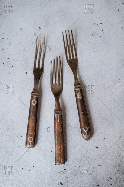 Trio of vintage forks on a speckled background