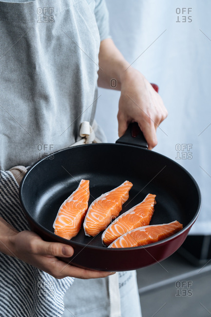 Chef holding a pan with a serving of 4 salmon strips
