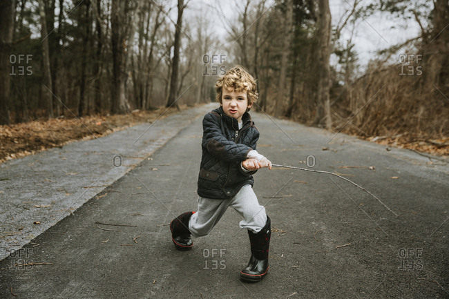Full length portrait of cute boy playing with stick on road