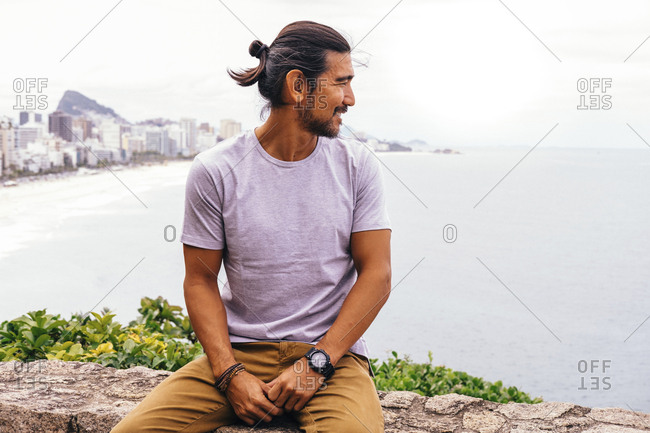 Smiling mature man looking at sea while sitting on retaining wall in city