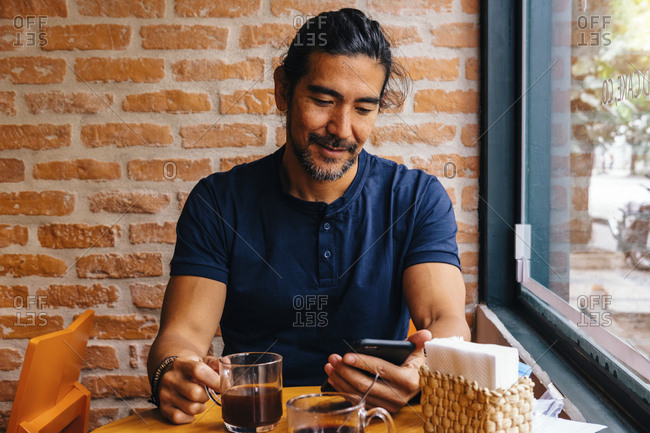 Mature man with black coffee using smart phone against brick wall in cafe