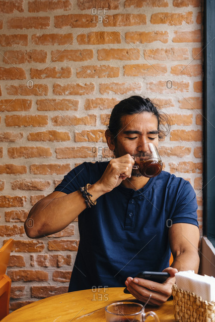Mature man drinking black coffee against brick wall in cafe