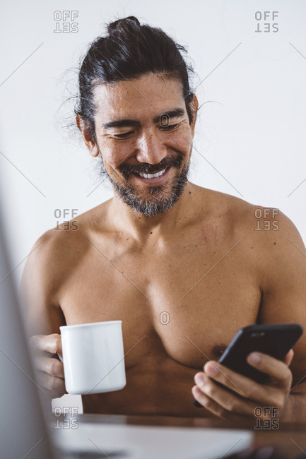 Shirtless smiling man with coffee cup using mobile phone while sitting against wall at home