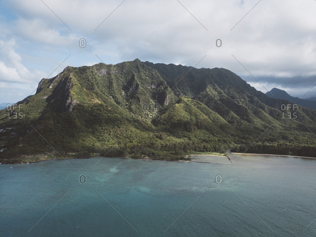 Scenic view of mountain by sea against cloudy sky