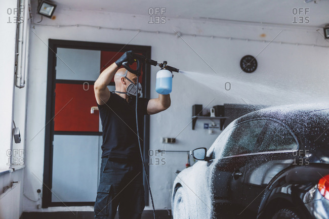 Worker pouring water on car while standing in workshop