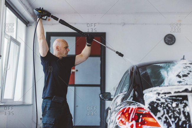 Confident worker pouring water on car with hose in workshop