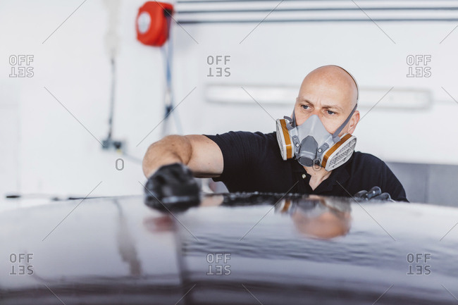 Male worker wearing protective mask while cleaning car roof in workshop