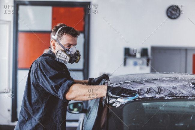 Side view of male worker cleaning car roof with soap in workshop