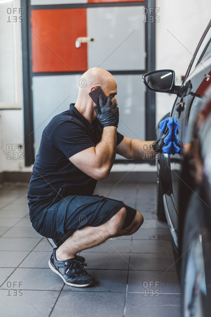 Side view of male worker talking on smart phone while cleaning car with towel in workshop